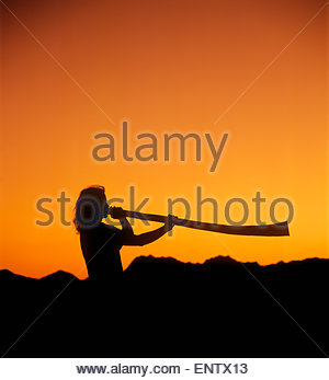 Silhouette Musician playing Didgeridoo wind instrument with orange fading sunset sky and mountains background. Tucson - Stock Image