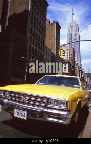 Yellow cab and Empire State Building New York USA - Stock Image