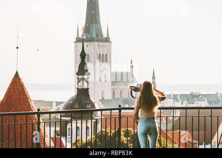 Young woman traveling in Tallinn city vacations in Estonia weekend Lifestyle outdoor girl tourist sightseeing St Olav's Church Old Town architecture - Stock Image