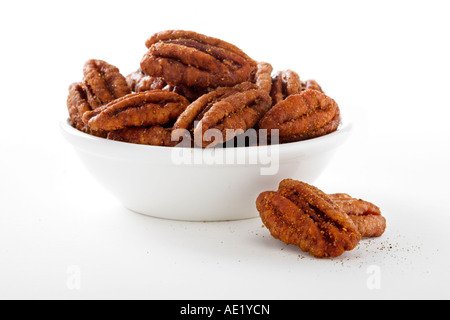 A bown of spiced pecans with white background cutout - Stock Image