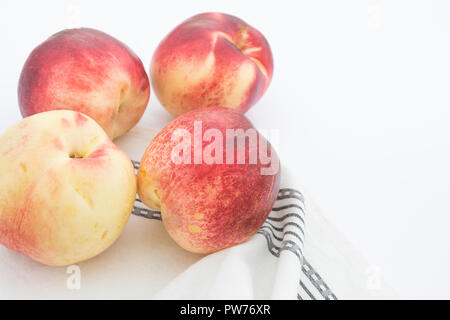 Ripe raw beautiful colorful red yellow nectarines on white kitchen table cotton towel. Harvest vitamins healthy lifestyle concept. Food poster with co - Stock Image