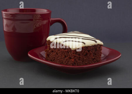 Three reds seens in red velvet cake, crimson mug, and matching plate against black background offer casual, holiday appeal. - Stock Image