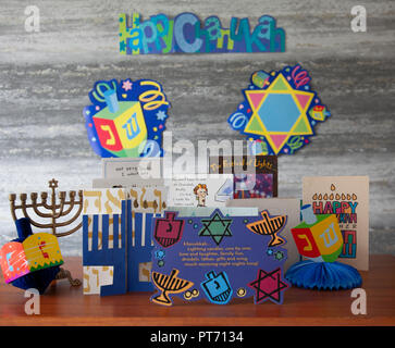 Selections of greetings cards, a chanukiah and decorative dreidls and defocussed wall decor. Jewish festival of Hanukkah aka chanukkah, Chanukah, - Stock Image