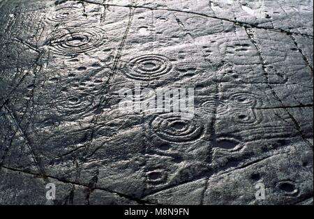Cup and ring mark marks prehistoric Neolithic rock art on natural rock outcrop at Achnabreck in Kilmartin Valley, - Stock Image