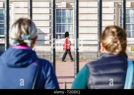 London, UK - October 3, 2018 - Back view of two tourists watching a sentry of Grenadier Guards patrolling outside Buckingham Palace - Stock Image