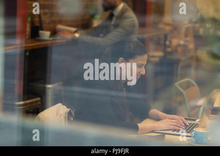 Smiling businesswoman working at laptop in cafe - Stock Image