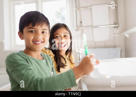 Portrait happy brother and sister brushing teeth in bathroom - Stock Image