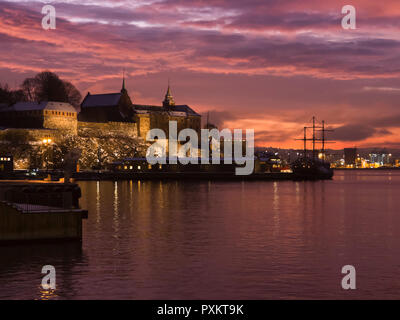 The fortress Akershus Castle in the centre harbour district of Oslo Norway silhouetted against a beautiful red winter sunrise - Stock Image