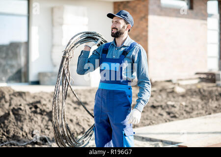 Portrait of a handsome electrician in uniform with power cable for the network on the construction site - Stock Image