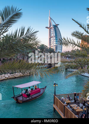 The Burj al Arab emerges from between the fronds of palm trees as boats glide past along the waters of Souk Madinat in Dubai. - Stock Image
