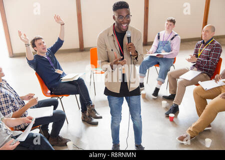 Man with microphone talking, leading group therapy - Stock Image
