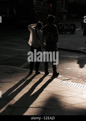 Couple standing in the street casting shadows in the sunlight - Stock Image