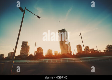 Sunset in residential district with many houses, street lantern in front, part of highway and flying seagull, Barcelona - Stock Image