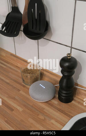 grey Google Home Mini device on a kitchen counter - Stock Image