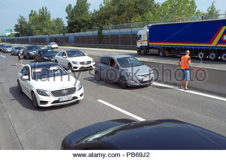 A man wearing a hi-viz vest watches passing traffic as the westbound A1 autobahn is at a standstill (due to serious accident), near Haag, in Austria - Stock Image