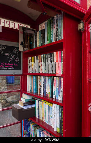 Old red telephone kiosk converted to use as a book exchange in the village of Collingtree, Northamptonshire, UK - Stock Image