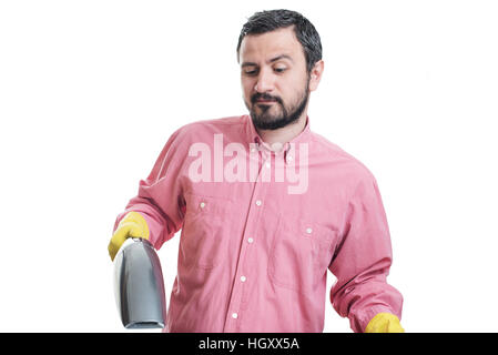 Smiling young man with handheld vacuum cleaner - Stock Image