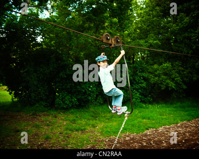 Girl on flying fox in adventure playground, New Zealand. - Stock Image