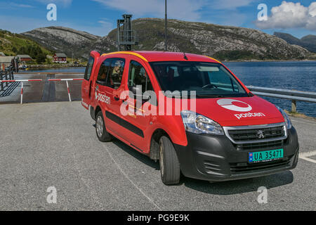 Oldeide, Norway, July 25, 2018: Norwegian mail van is parked next to ferry docking as its operator waits for the ferry to deposit mail on board. - Stock Image