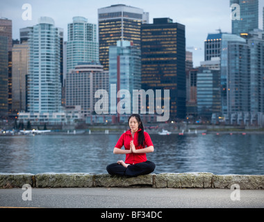 Asian woman does yoga Padmasana Lotus Pose along the Stanley Park seawall with the city skyline beyond, Vancouver, - Stock Image