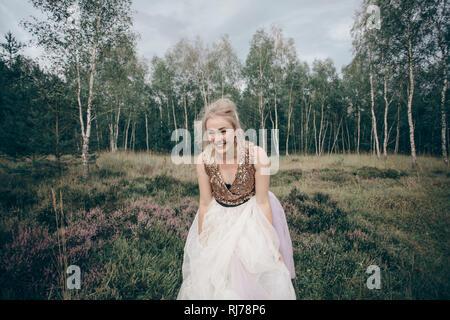 junge blonde Frau präsentiert Kleid inmitten von Besenheide - Stock Image