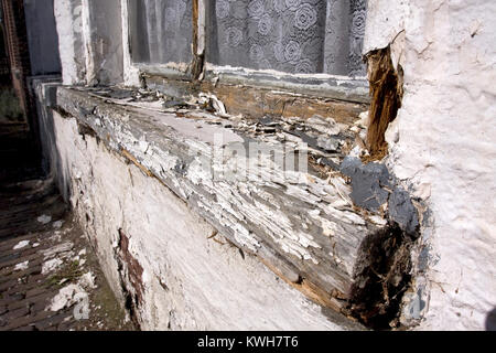 White paint peeling of an old, badly maintained, rotten, wooden windows frame. - Stock Image