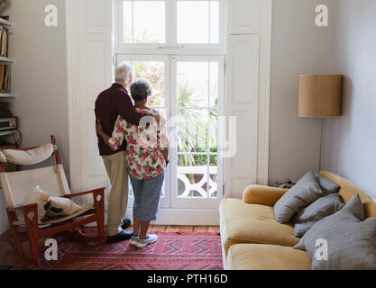 Affectionate, serene senior couple looking out living room window - Stock Image