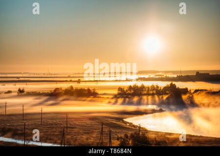 A warm dawn on a misty morning in the countryside. Summer fields - Stock Image