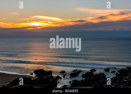 Long exposure sunset over surfers on Fistral Beach, Newquay, Cornwall, UK - Stock Image