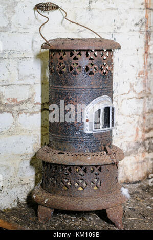 Old, antique paraffin heater, covered in rust.  Heaters like this were common in Irish homes at the start of the - Stock Image
