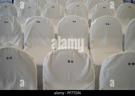 Chairs, covered with white bedspreads with numbers - Stock Image