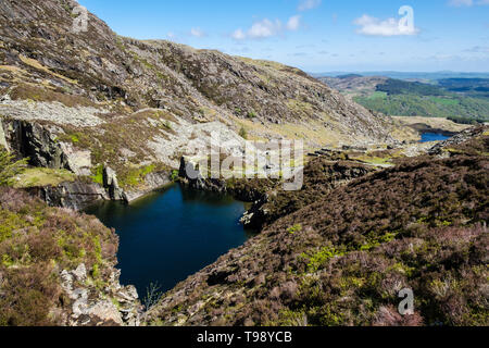 Flooded disused slate quarry pit and slag heaps on path route to Carnedd Moel Siabod mountain in Snowdonia National Park. Capel Curig Conwy Wales UK - Stock Image
