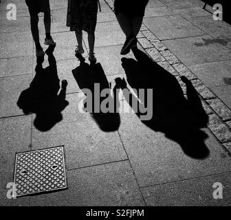 The shadows of two children as they walk along the pavement with their mother. Is it a family outing? Have they been abducted? An image with lots of potential uses. Photo - © COLIN HOSKINS. - Stock Image