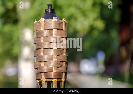 Close-up bamboo torches oil lamp on nature background. - Stock Image