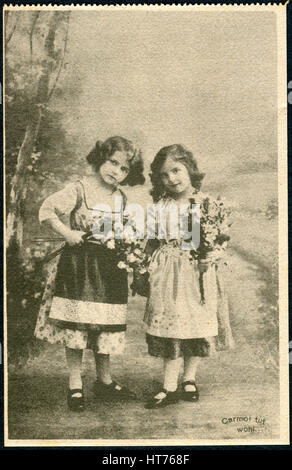 GERMANY - CIRCA 1914: A promotional postcard (Carmol tut wohl) printed in Germany, shows two little girls with bouquets - Stock Image