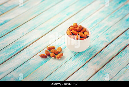 Crude almonds on a vintage wooden table. Organic Food. Nuts - Stock Image