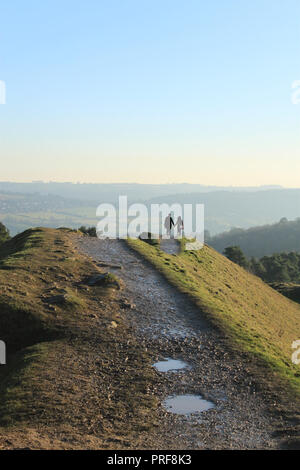 Young couple standing hand in hand on a hill looking at the view on a winter's day.  Painswick Beacon. - Stock Image