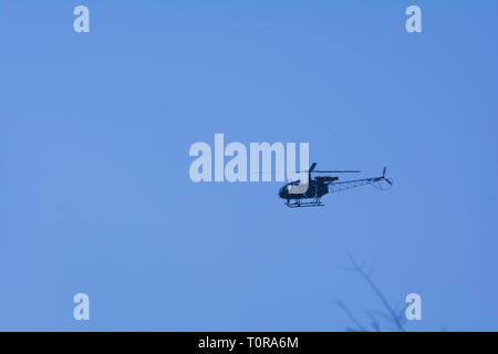 A small helicopter flying in the sky - Stock Image