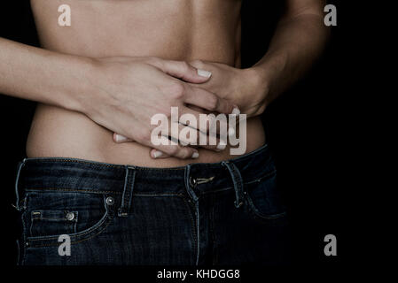 Woman placing hands on bare stomach, cropped - Stock Image
