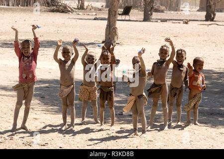 Africa, Namibia, Opuwo. Himba children waving good-bye. Credit as: Wendy Kaveney / Jaynes Gallery / DanitaDelimont.com - Stock Image
