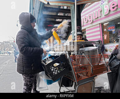 On a cold winter day, two women selling freshly grilled corn. On 82nd St. in Jackson Heights, Queens, New York under the #7 train stairway. - Stock Image