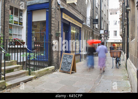 Two elderly ladies walk down a small shopping street in Cambridge with colourful umbrellas - Stock Image