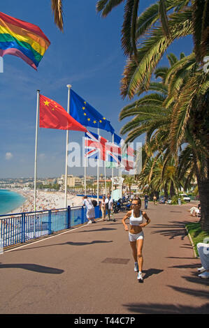 Nice Cote dAzur France - A jogger runs past flags on the Promenade des Anglais - Stock Image