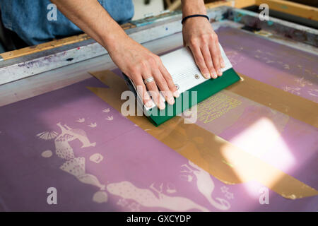 Hands of young male printer using squeegee in printing press studio - Stock Image