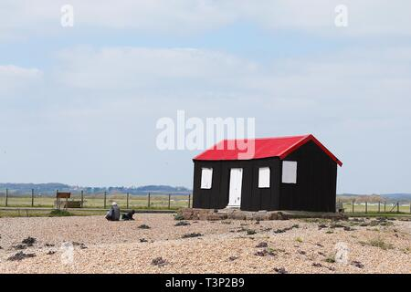 Rye, East Sussex, UK. 11th Apr, 2019. UK Weather: Cloudy intervals with blustery winds on the Rye harbour nature reserve as a few people take a walk along the many scenic routes. The red shed at Rye Harbour Nature Reserve. Credit: Paul Lawrenson 2019, Photo Credit: Paul Lawrenson/Alamy Live News - Stock Image