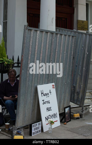 London, UK. 17th June 2019. Hunger striker Richard Ratcliffe behind an iron board, placed there by Iranian embassy staff and builders today, in front of the Iranian embassy in London protesting the detention of his wife Nazanin Zgahari in Iran over spying allegations. Credit: Joe Kuis / Alamy - Stock Image