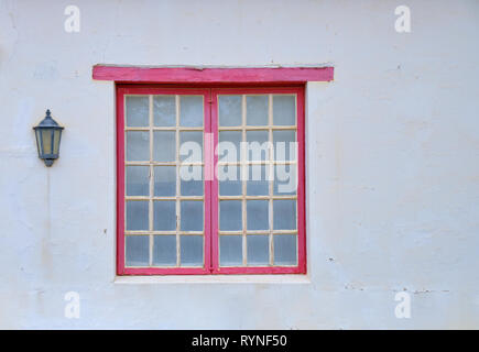 Minimalist capture of a single rural window on a white textured wall.  Window has small panels, and a red window frame. There is a house light - Stock Image