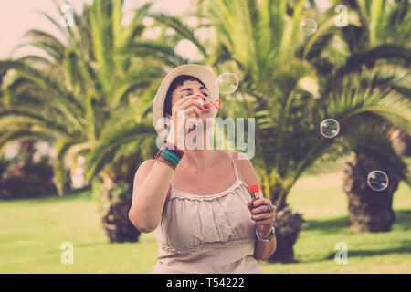 Young cute caucasian female play and have fun doing soap bubbles outdoor at the tropical park - enjoying leisure activity with kid play - no stress pe - Stock Image
