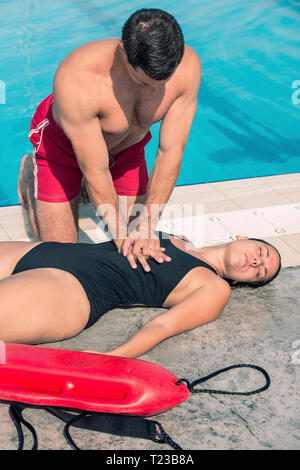 Lifeguard doing CPR after swimming pool accident. Toned image. - Stock Image