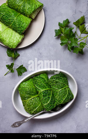 cabbage rolls from savoy cabbage on gray concrete background. view from above - Stock Image